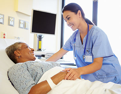 Asian nursing assistant with elderly patient in bed