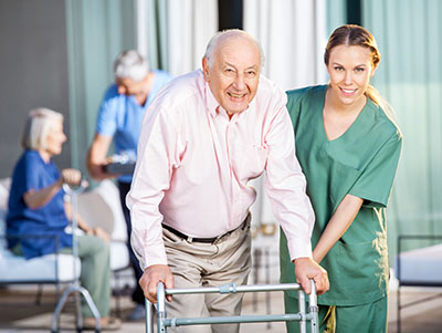 CNA helping elderly patient at nursing home