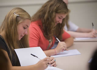 girl-college-students-writing-in-class