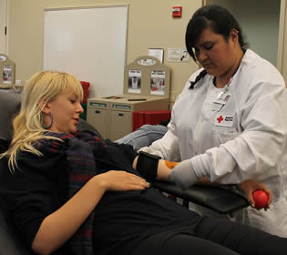 red-cross-worker-taking-blood-pressure
