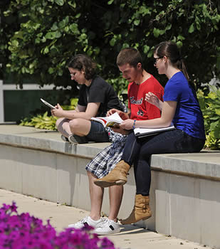 students-sitting-on-college-campus