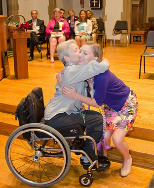 nursing-grad-hugging-elderly-woman-in-wheelchair